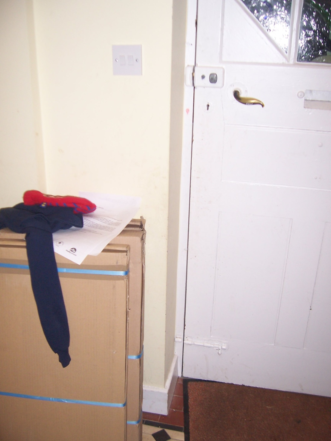 Boxes leaning by front door with jumper and papers resting on them