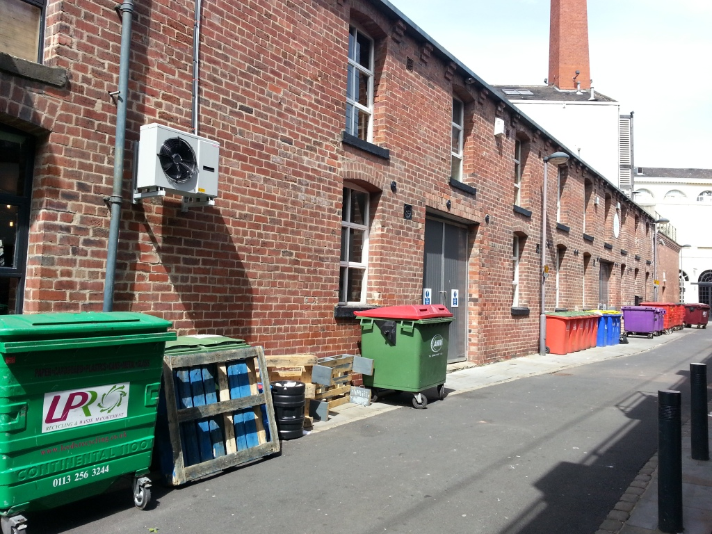 Red brick, air con units and recycling bins