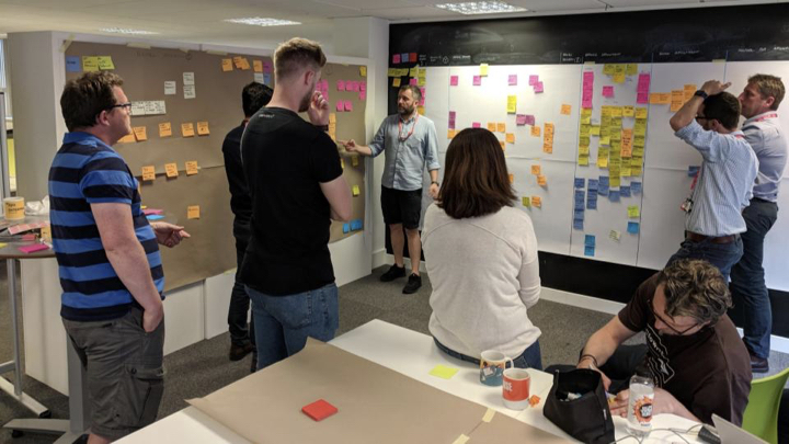 People looking at sticky notes on two walls
