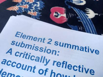 "Document on table cloth. Text visible: ""Element 2 summative submission: A critically reflective account"""