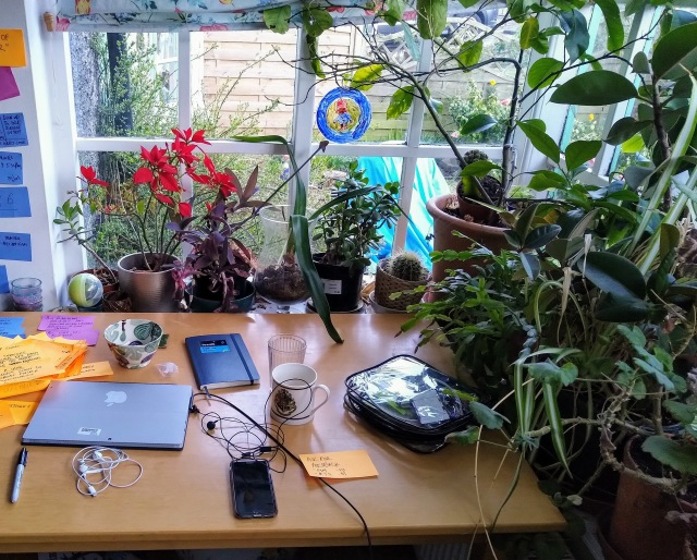 Desk with laptop, phone and notebook in front of window and surrounded by houseplants