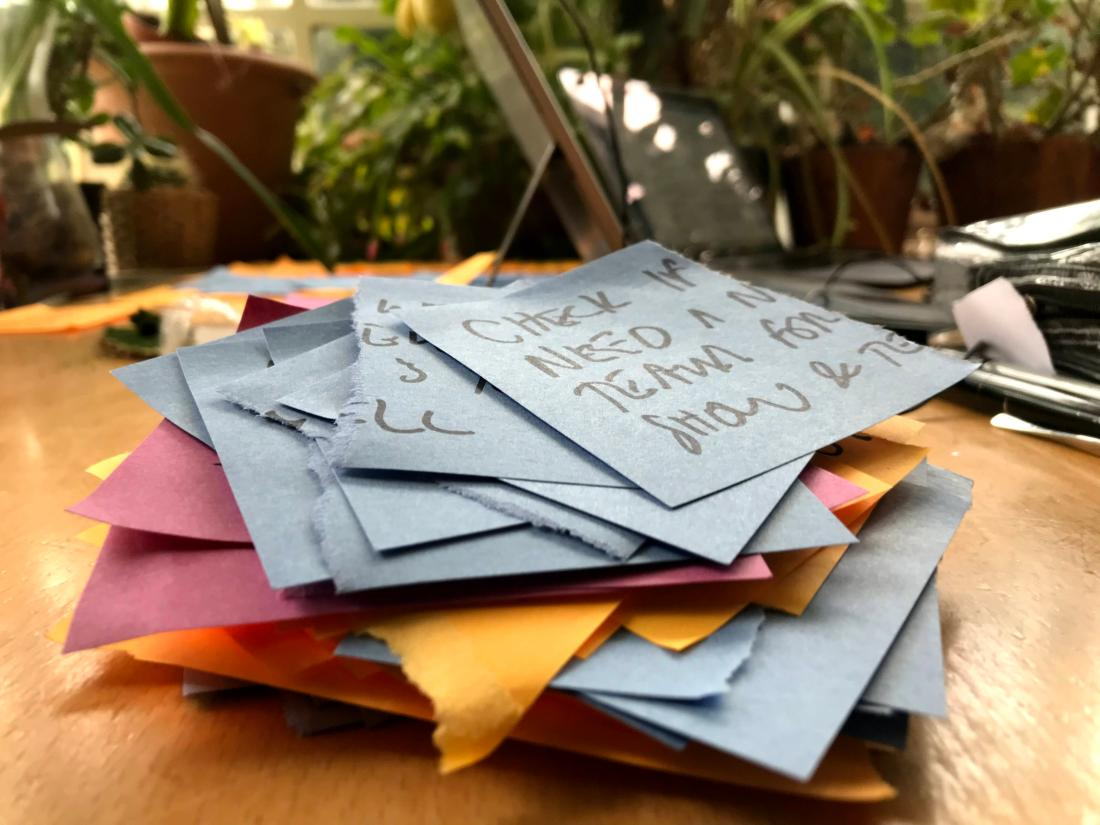 Pile of torn-up sticky notes on wooden table in front of houseplants