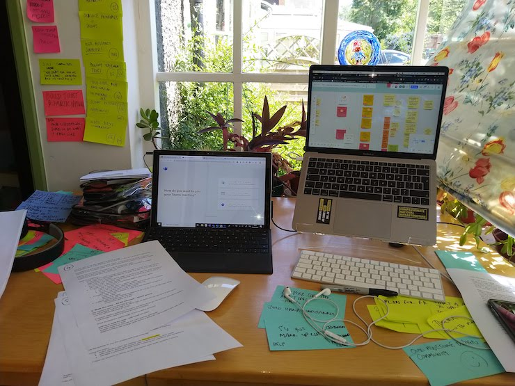 Two laptops on desk surrounded by sticky notes and papers