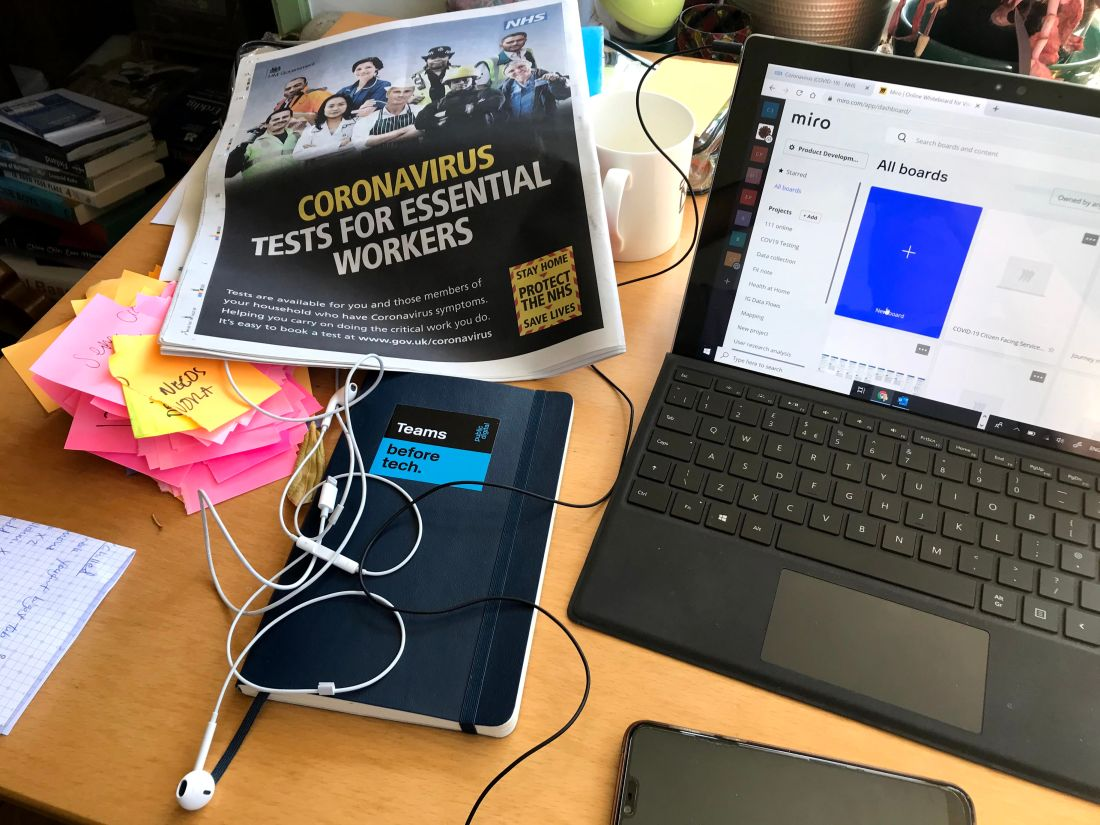 "Desktop with newspaper showing ""coronavirus tests for essential workers"", notebook with sticker that says ""teams before tech"", torn up sticky notes, laptop with Miro open in browser"