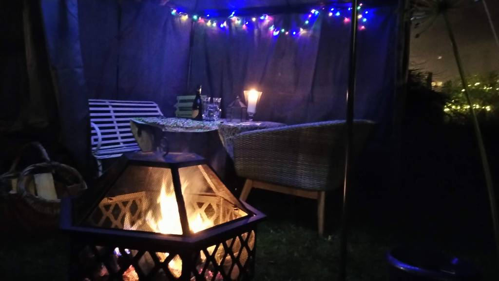 Fire bowl with fire, gazebo with coloured fairy lights, and a bottle of prosecco on a table between garden seating
