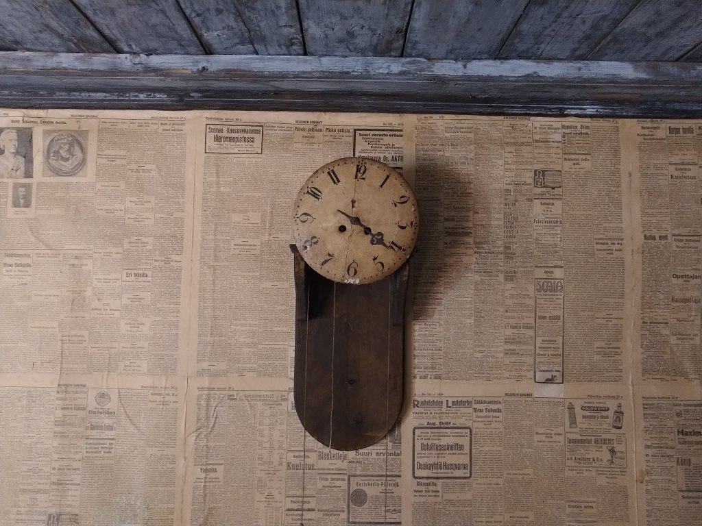 Old analogue clock hanging on a wall papered with old newspaper pages