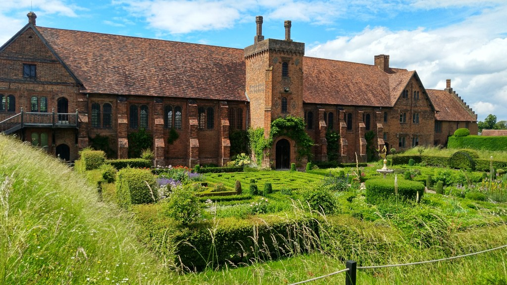 Red brick, red tile-roofed 16th Century palace with garden including box hedges, grasses and flowers