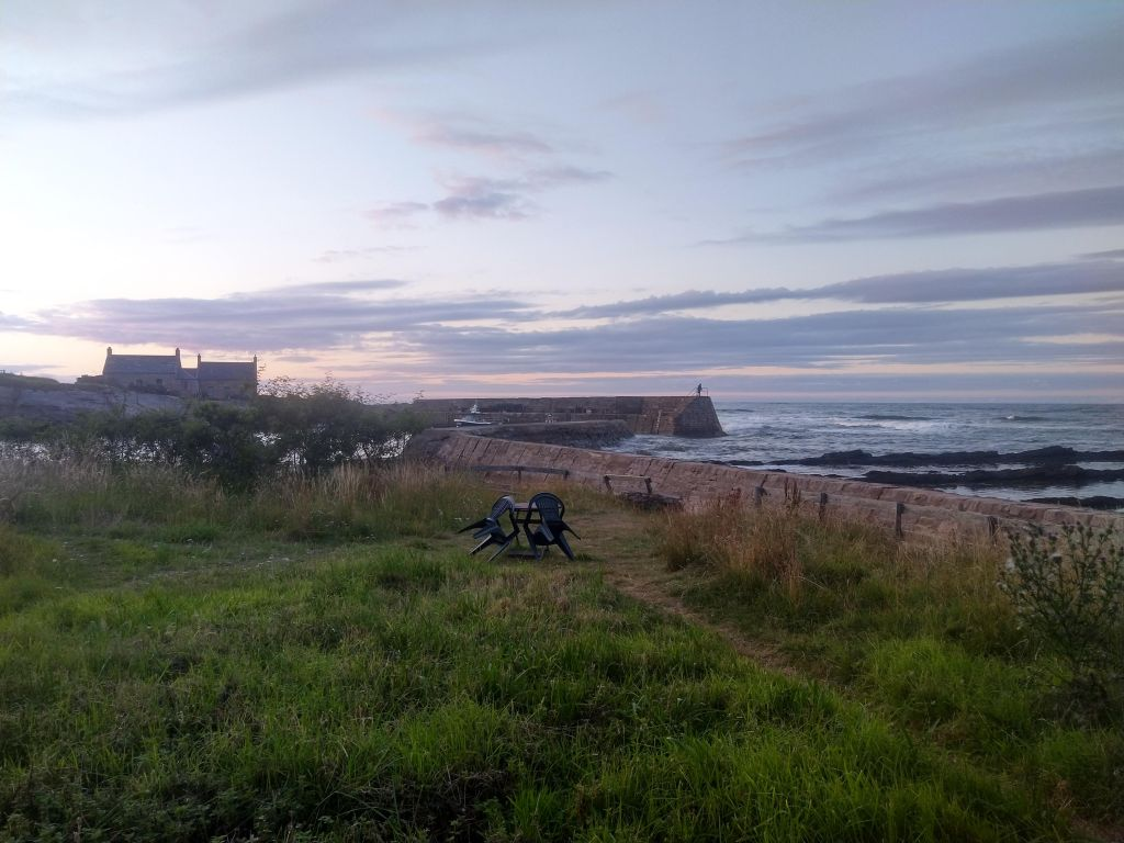 Grass in front of sea wall with rocks and waves behind. In the distance two small stone buildings and a harbour wall