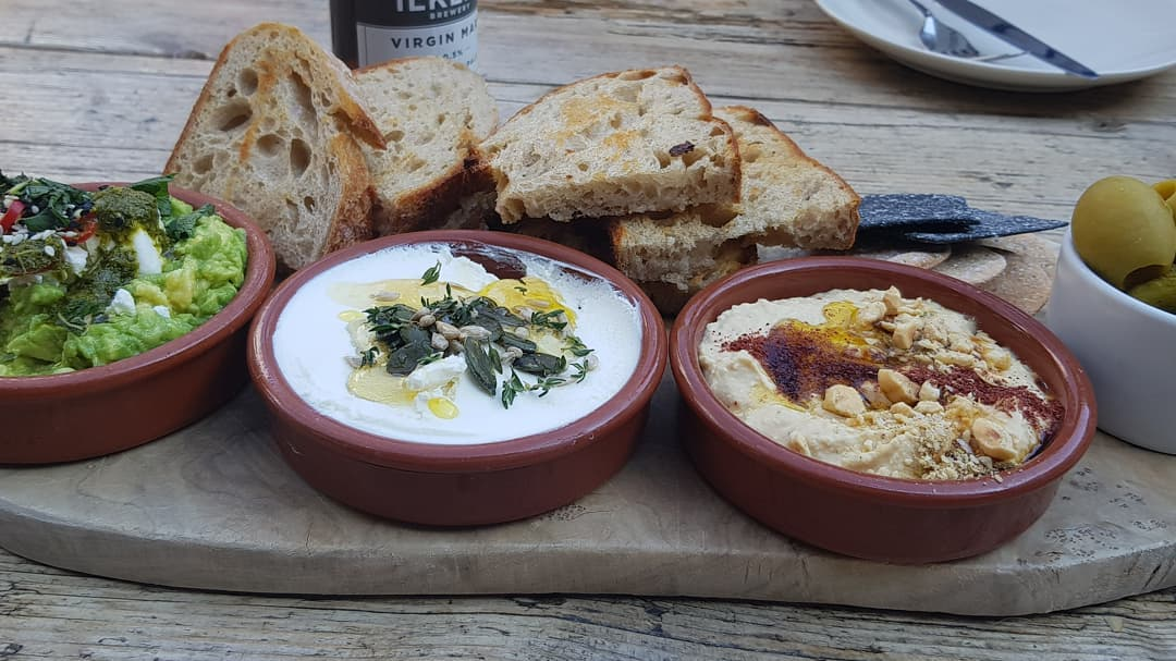 Small dishes of guacamole, whipped cheese and hummus with toasted bread on wooden board